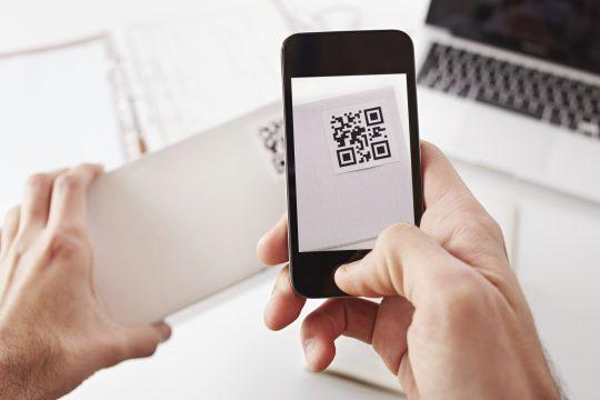 celular escaneando caixa com QR Code