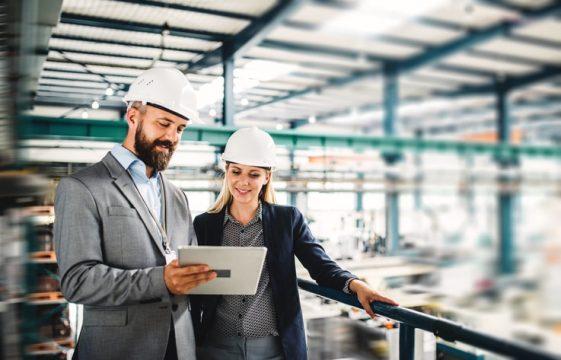 homem e mulher olhando o tablet em uma indústria