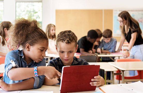 Crianças em sala de aula utilizando um tablet