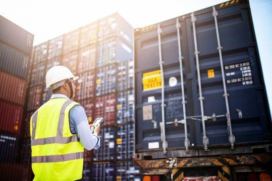 homem com celular na mão olhando para um container de carga